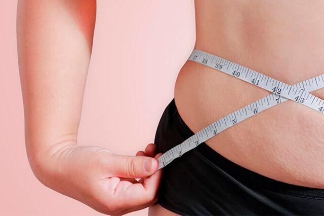 Foco suave em mulher com uma fita métrica conferindo a medida corporal da barriga