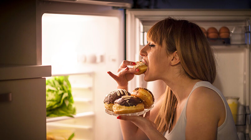 Foco na imagem de uma jovem mulher com transtorno alimentar fazendo um lanche da meia-noite, comendo rosquinhas na frente da geladeira